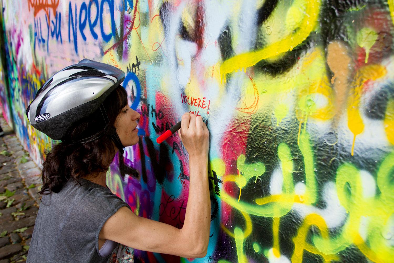 Dejando huella en el muro de John Lennon en Praga